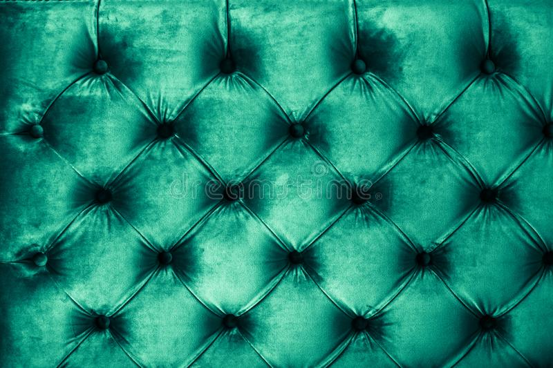Emerald luxury velour quilted sofa upholstery with buttons, elegant green home decor texture and background royalty free stock images