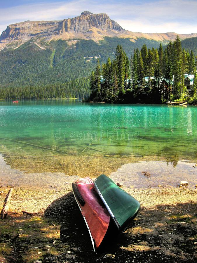 Emerald Paradise. Two canoes ready to hit the crystal clear Emerald Lake in the vast beautiful landscape of Yoho National Park, British Columbia Canada stock photography