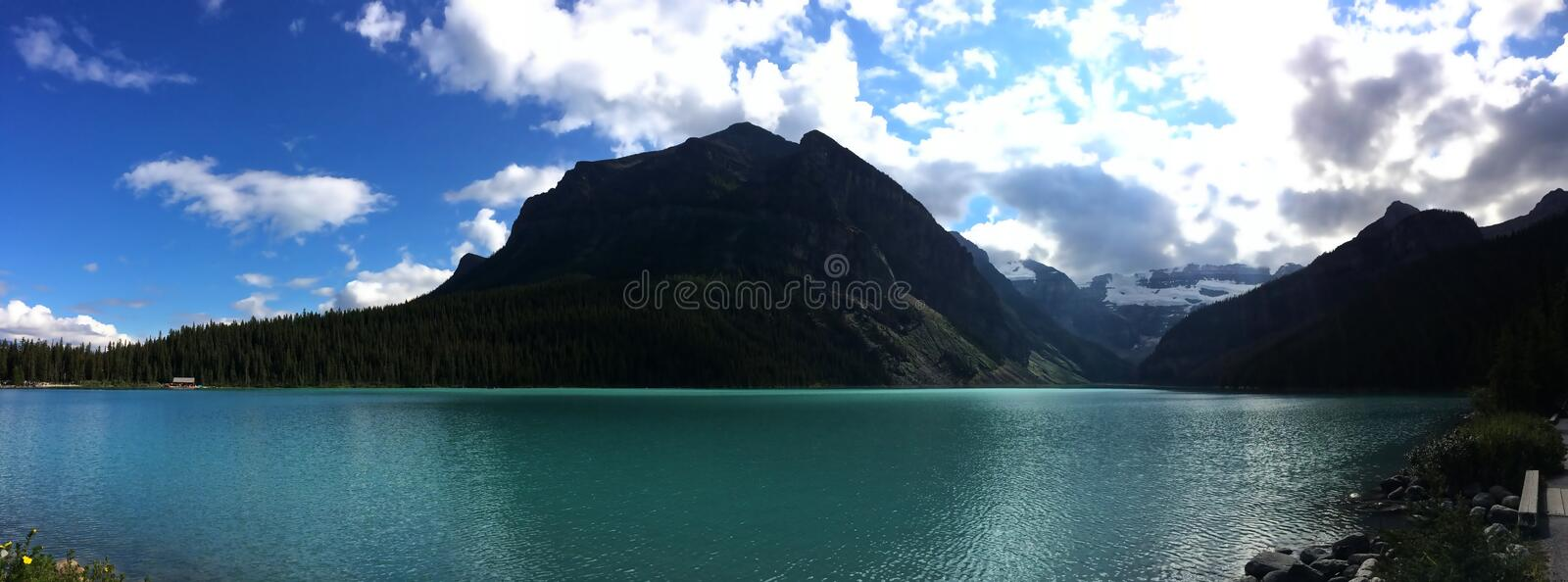 Emerald waters of Lake Louise. Lake Louise, named Lake of the Little Fishes by the Stoney Nakota First Nations people, is a glacial lake within Banff National royalty free stock images