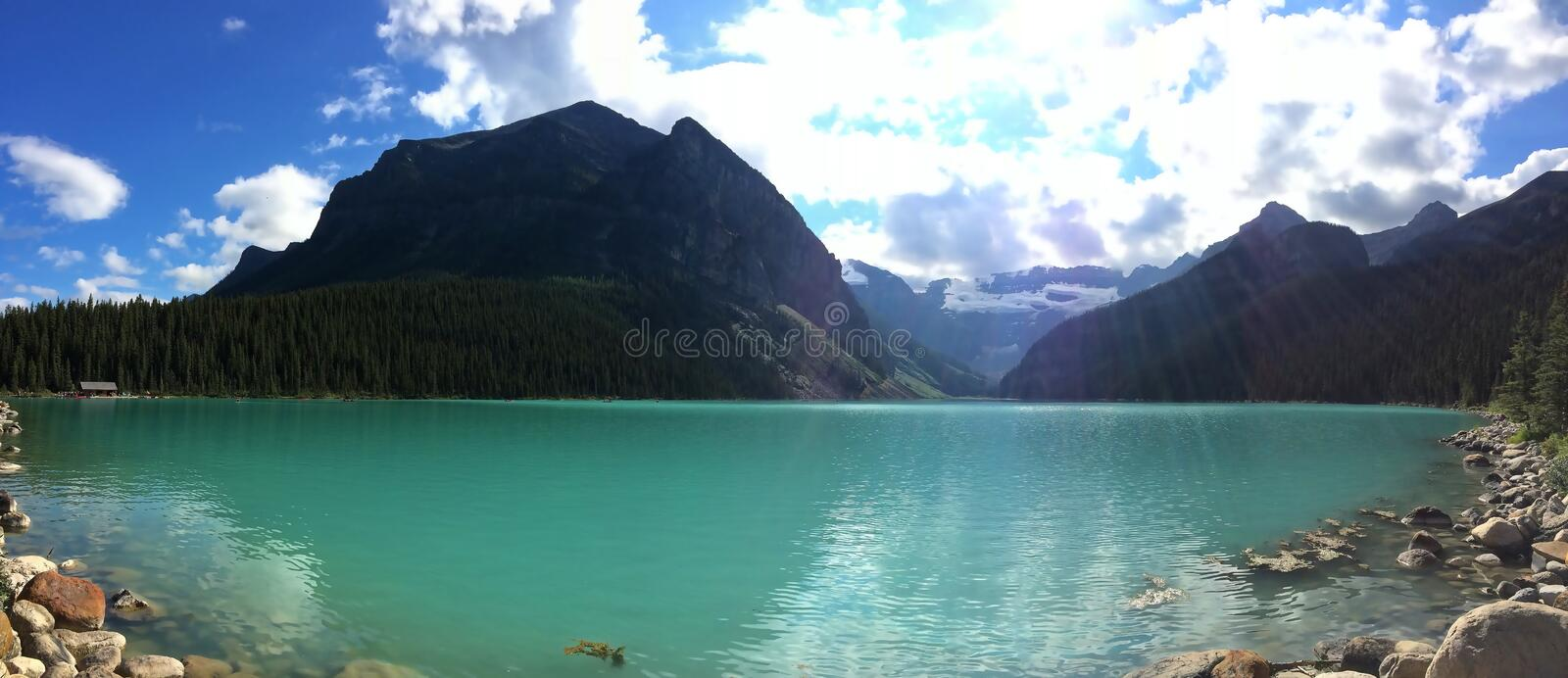 Emerald waters of Lake Louise. Lake Louise, named Lake of the Little Fishes by the Stoney Nakota First Nations people, is a glacial lake within Banff National royalty free stock photo