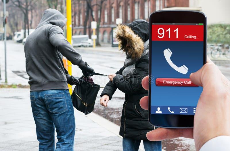 A emergência discada da mão da pessoa chama o telefone celular fotografia de stock