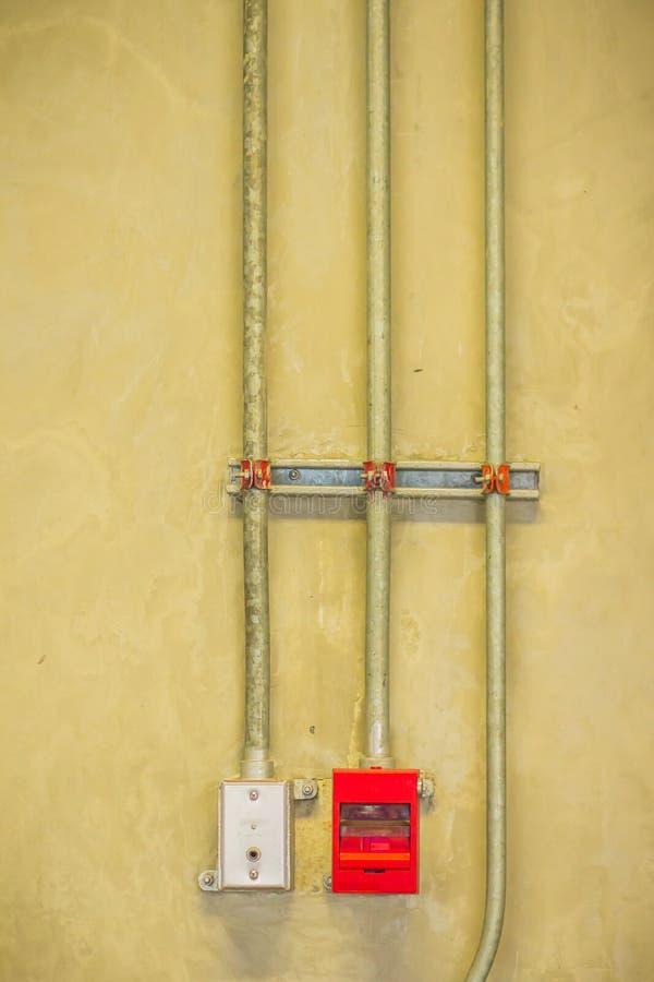 A emergência vermelha e os bombeiros da caixa de tração do alarme de incêndio telefonam com o encanamento da canalização no muro  fotos de stock royalty free
