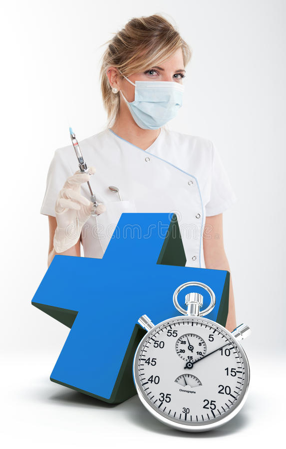 Emergency dental care. Female dentist holding a syringe, a blue cross and a chronometer stock photo