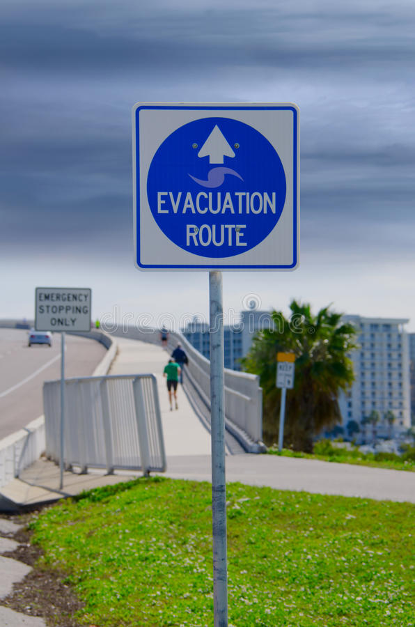 Emergency Evacuation Route sign and running people. An emergency Evacuation Route sign with stormy skies and running people in the background royalty free stock image