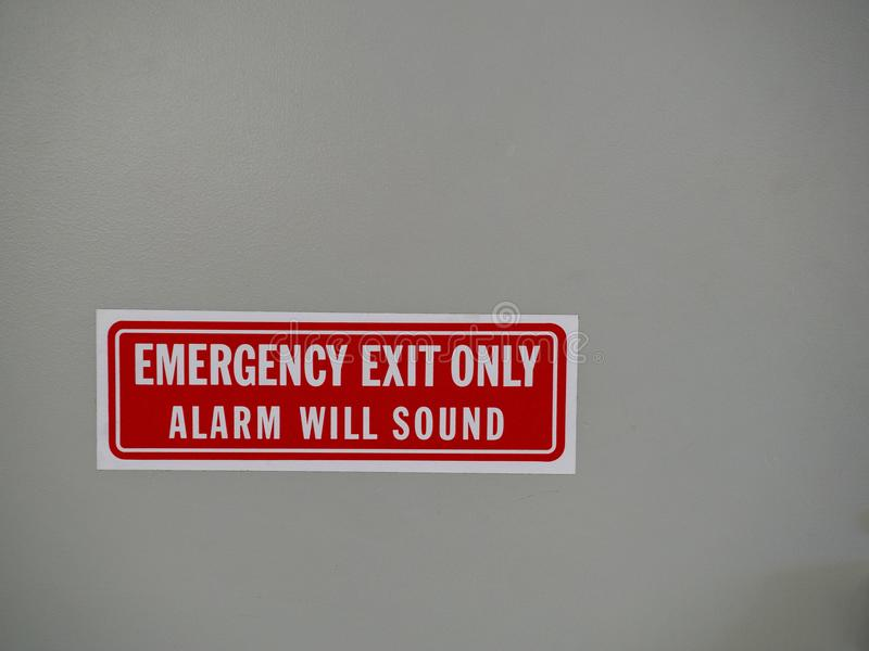 Emergency exit only, alarm will sound sign posted on a white door. An emergency exit only, alarm will sound sign posted on a white door royalty free stock photo