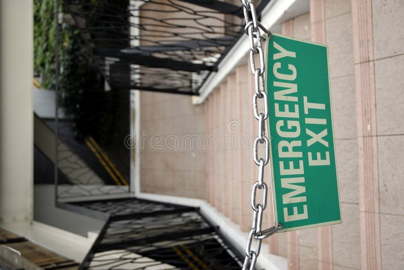 Emergency exit - Chained. An emergency exit blocked by a chained up sign saying Emergency exit - the irony stock photos