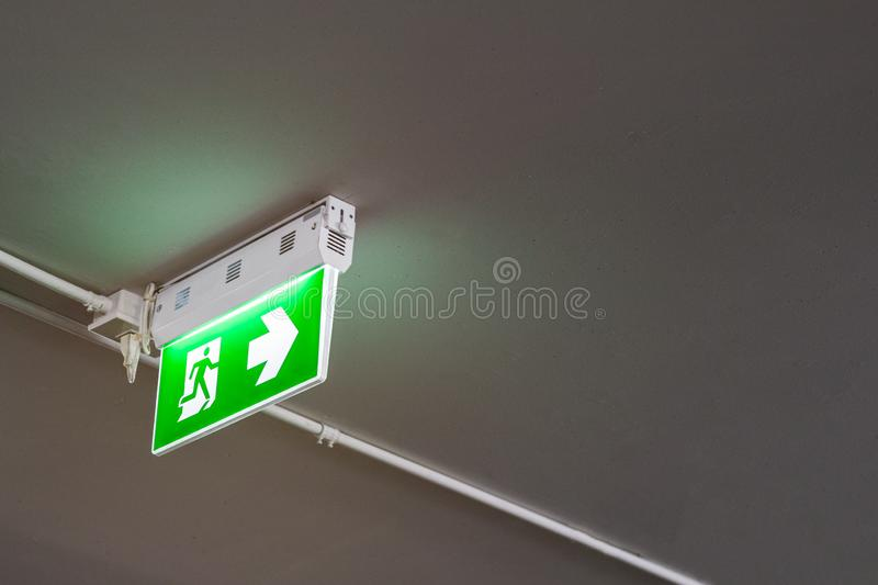 Emergency exit sign with right arrow in department store underground car parking. Safety first concept. Copy space wallpaper royalty free stock images