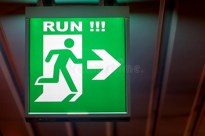 The emergency exit sign RUN!. Shows the direction of escape in case of danger. The emergency exit board hangs on the ceiling of the building royalty free stock images