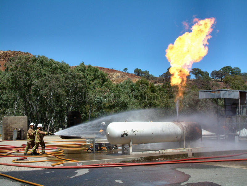 Emergency Fire Fighter Crew fighting a huge gas fire. Featuring a gas tank burning out of control in a bush fire after a 911 - 000 emergency call stock photo