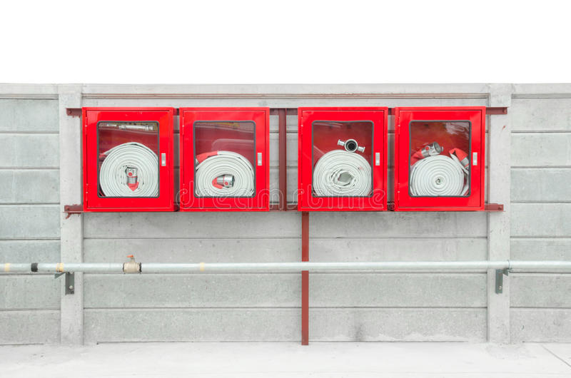 Emergency fire hose inside a glass fronted box mounted on a wall. Attached to a metal hydrant to provide water flow and pressure in an emergency stock images
