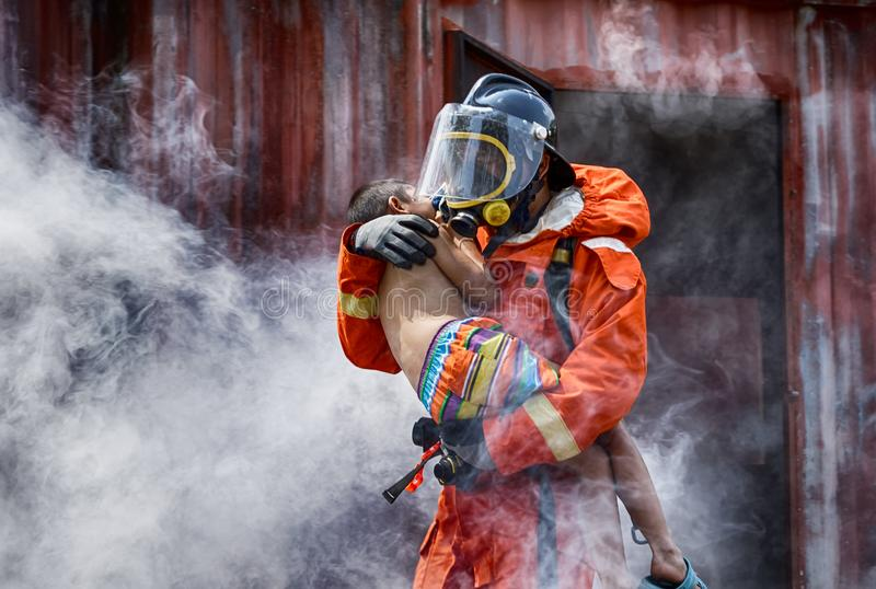 Emergency Fire Rescue training, Firefighters save the boy from bu stock images