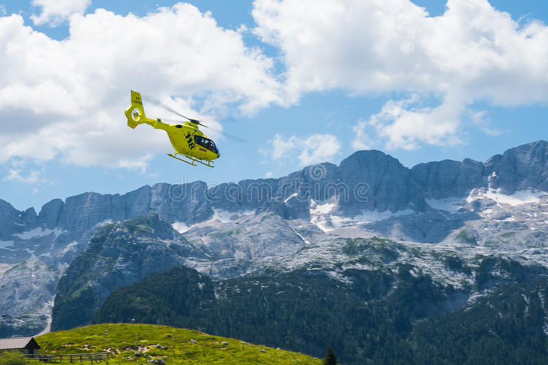 Emergency helicopter hovering over the mountains. In a sunny day with couds. 112 Emergency service Sella Nevea Italy - July 2017 royalty free stock image