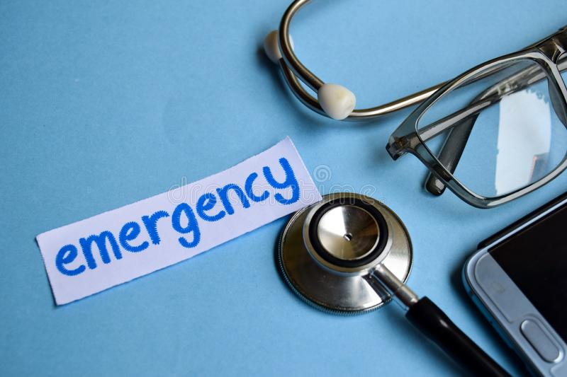 Emergency inscription with the view of stethoscope, eyeglasses and smartphone on the blue background. royalty free stock photo
