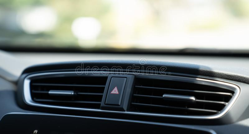 Emergency light button on dashboard of car between air vents. Emergency light button on dashboard of car between two air vents stock photo
