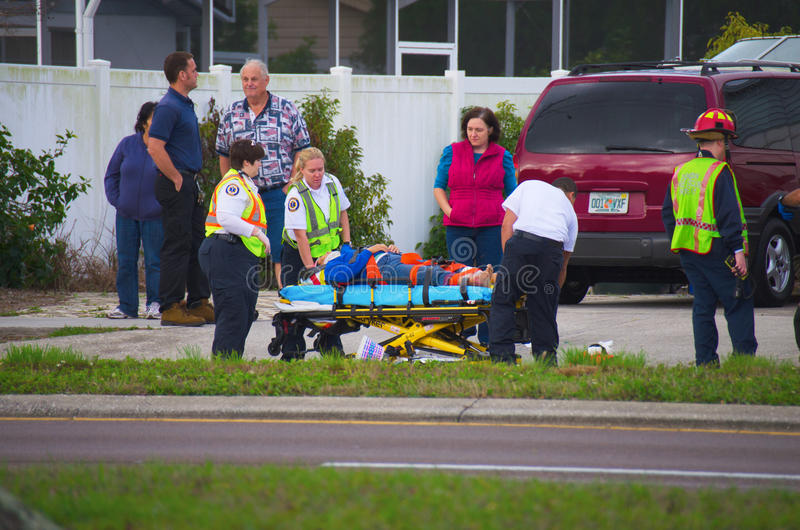 Emergency response to injured pedestrian. An emergency response ambulance and fire rescue assisting an injured pedestrian that was riding a bike and was struck stock images