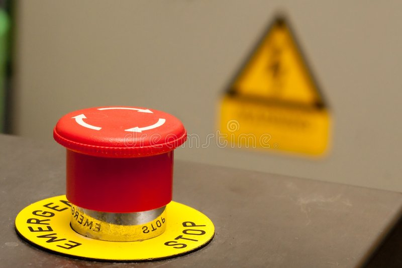 Emergency Stop. Button, with a warning of electrical hazard in the background royalty free stock photo