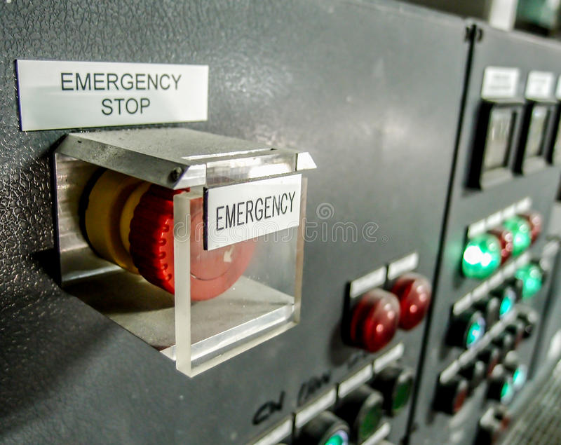 Emergency stop button at control panel. In a factory stock image