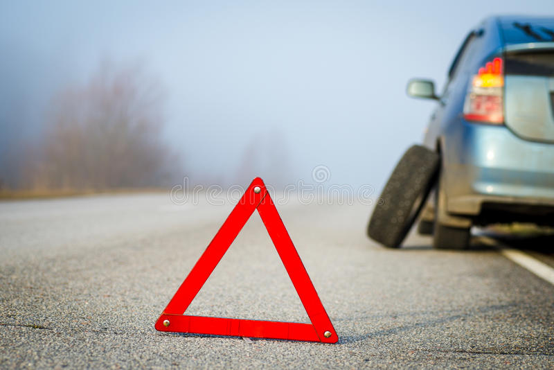 Emergency stop sign in background with broken blue car. Emergency stop sign. Blue car punctured tire. Empty road in a foggy day royalty free stock images
