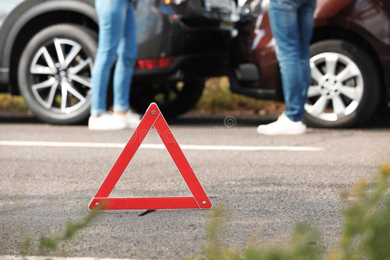 Emergency stop sign near people discussing car accident on road. Auto insurance stock photo