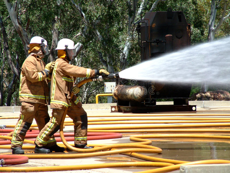 Emergency Teams fighting fire. Emergency Teams fighting a fire. Featuring a gas tank burning out of control in a bush fire after a 911 - 000 call with fire hose stock image