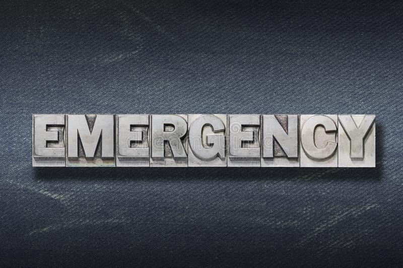 Emergency word den. Word made from metallic letterpress on dark jeans background stock photos