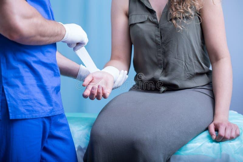 Emergency worker bandaging female hand. Close-up of emergency worker bandaging female hand stock image