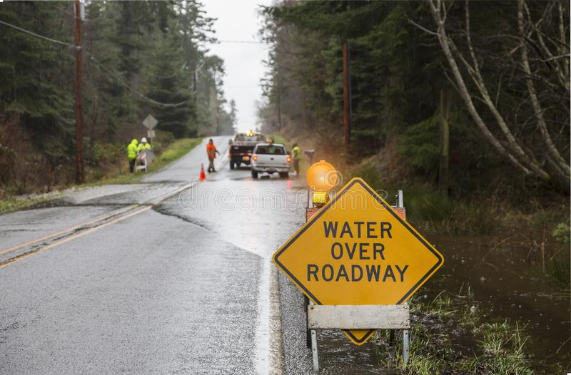 Emergency workers road crew placing warning signs on flooded highway. Hazards after a rain storm. Emergency workers road crew placing warning signs on flooded stock photo