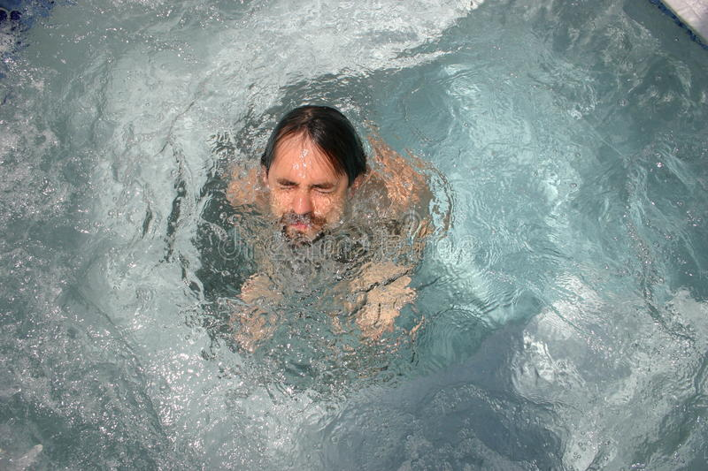 Emerging. Man coming out of the water in a pool royalty free stock photo
