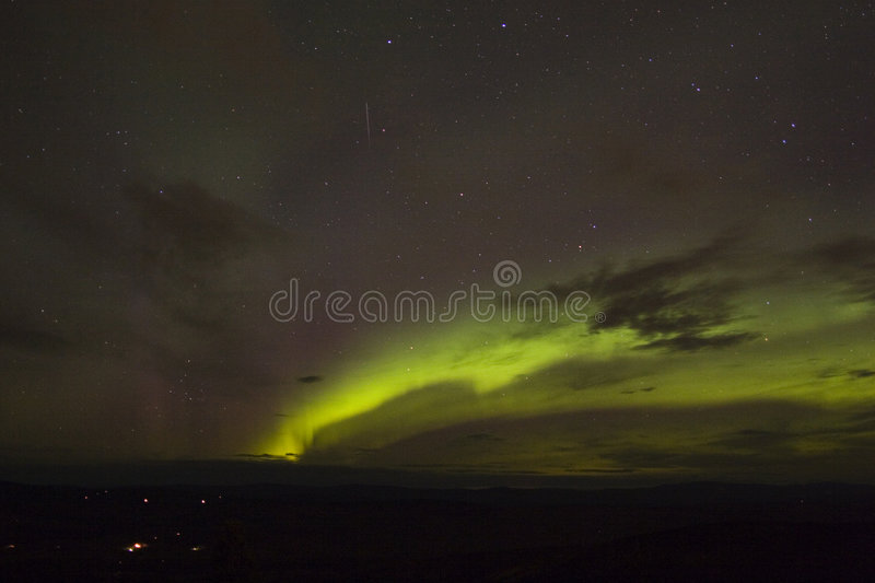 Emerging aurora arc with meteor royalty free stock photography