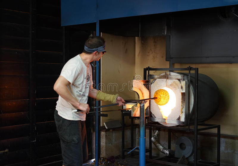 Emerging from the forge - glass art. A glassblower reclaims a molten, hand-blown glass bowl from the extreme heat of the forge stock image