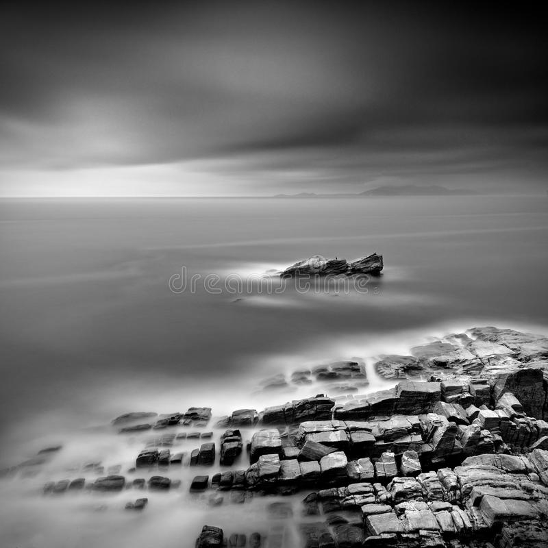Emerging Rock. Black and White, Long Exposure, Fine Art Seascape with Rocky Shore and a lonely rock royalty free stock images
