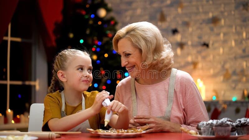 Emeryt dama patrzeje szczęśliwy Xmas czas, jak z podnieceniem dziewczyna dekoruje Xmas ciastka zdjęcia royalty free