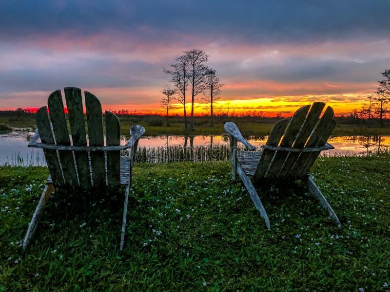 emerytura i dwa krzesła patrzeje zmierzch w bagnie fotografia royalty free