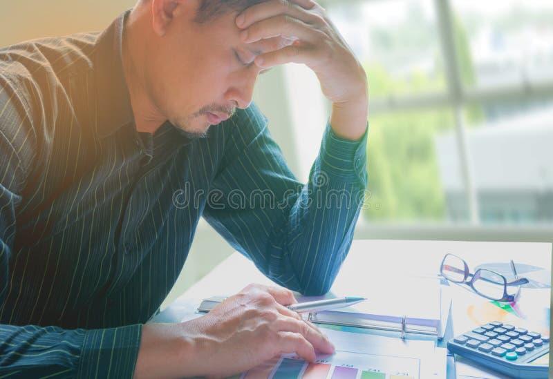 Emicrania dell'uomo d'affari con i problemi e sforzo nell'ufficio immagine stock