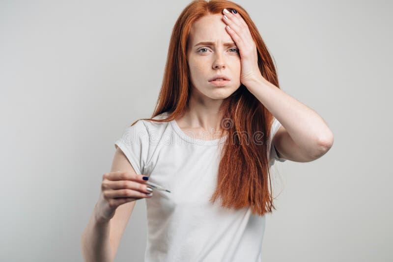 Emicrania Donna malata con il termometro che esamina macchina fotografica flu Freddo catturato donna fotografie stock libere da diritti