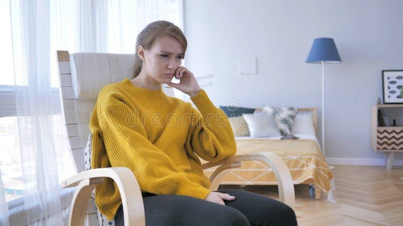 Emicrania, donna turbata di tempo che si siede sulla sedia casuale fotografia stock libera da diritti