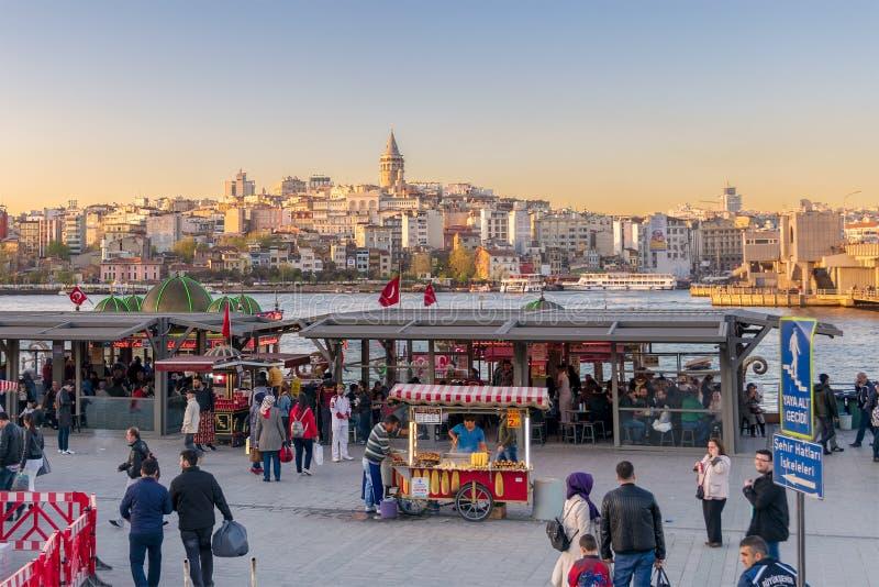 Eminonupiazza vóór zonsondergang met drijvende van de zeevruchtenrestaurants en stad mening die Galata-Toren, Istanboel, Turkije  royalty-vrije stock foto's