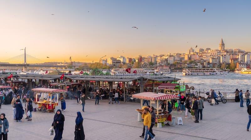 Eminonupiazza vóór zonsondergang met drijvende van de zeevruchtenrestaurants en stad mening die Galata-Toren, Istanboel, Turkije  stock fotografie
