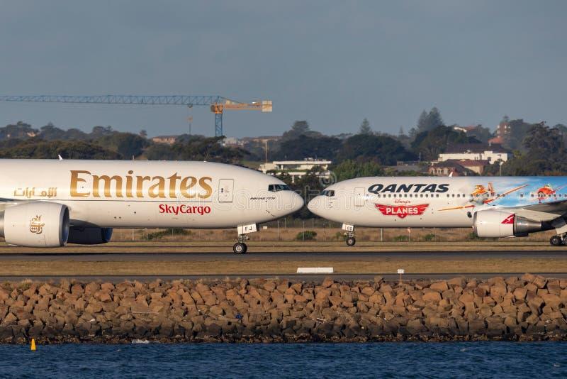 Emirat-Fracht Boeing 777 Frachtflugzeuge, die Qantas 767 auf dem Asphalt bei Sydney Airport führen stockfoto