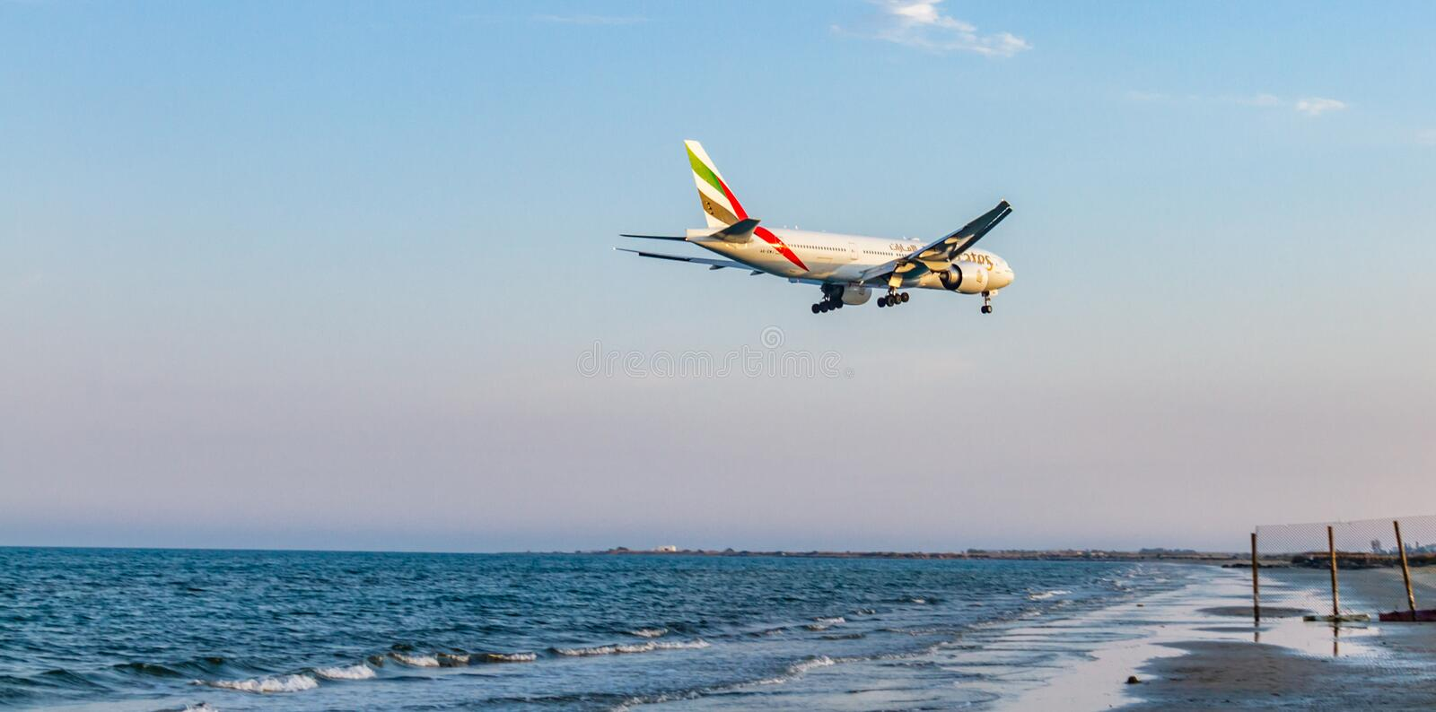 Emirates Airline Boeing 777 above the sea seconds before landing. Larnaca, Cyprus - April 29, 2018: Emirates Airline Boeing 777 above the sea seconds before royalty free stock image
