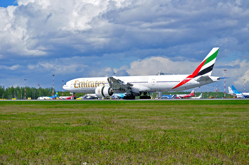 Emirates Airline Boeing 777 aircraft is landing in Pulkovo International airport in Saint-Petersburg, Russia. SAINT PETERSBURG,RUSSIA-MAY 11,2016. Emirates stock photos