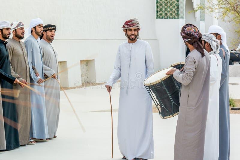 Emirati-Männer, die das Yowla, einen traditionellen Tanz im Erbe Arabische Emirates nahe bei einem historischen Gebäude durchführ stockfotografie