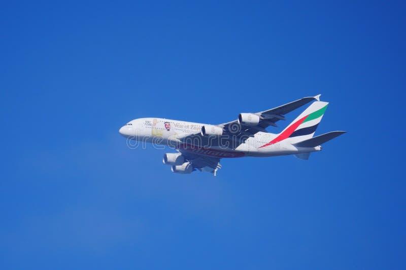 Emiratu samolot w głębokim niebieskim niebie w locie fotografia royalty free
