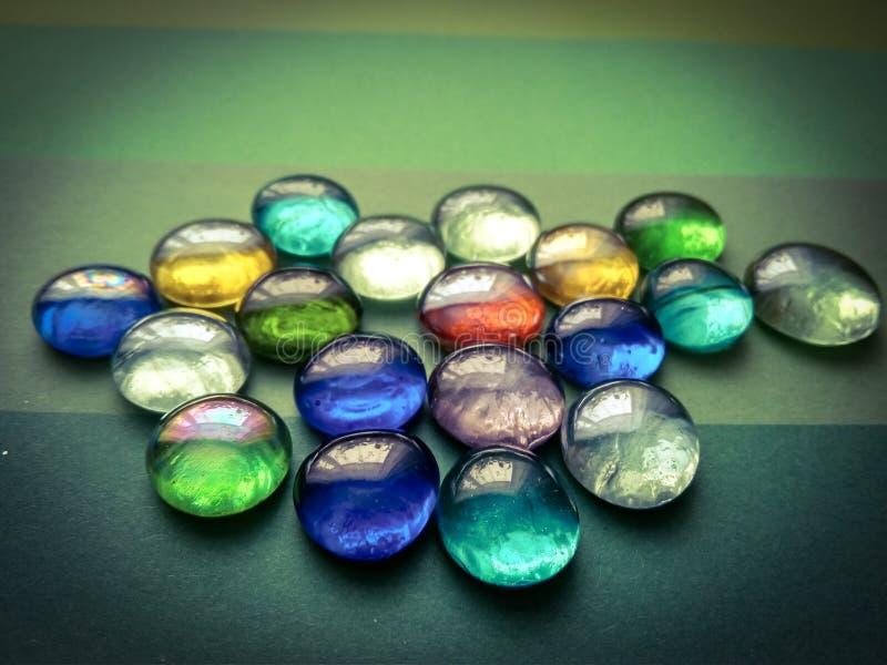 Emisferi di vetro colorati su un fondo verde immagini stock