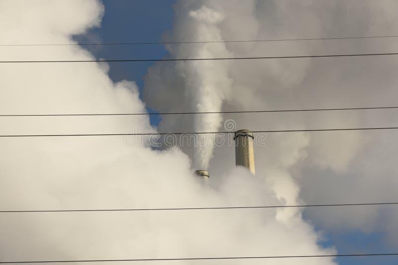 Emissões que aumentam de uma estação a carvão do central elétrica com fios elétricos da distribuição da grade no primeiro plano fotos de stock royalty free