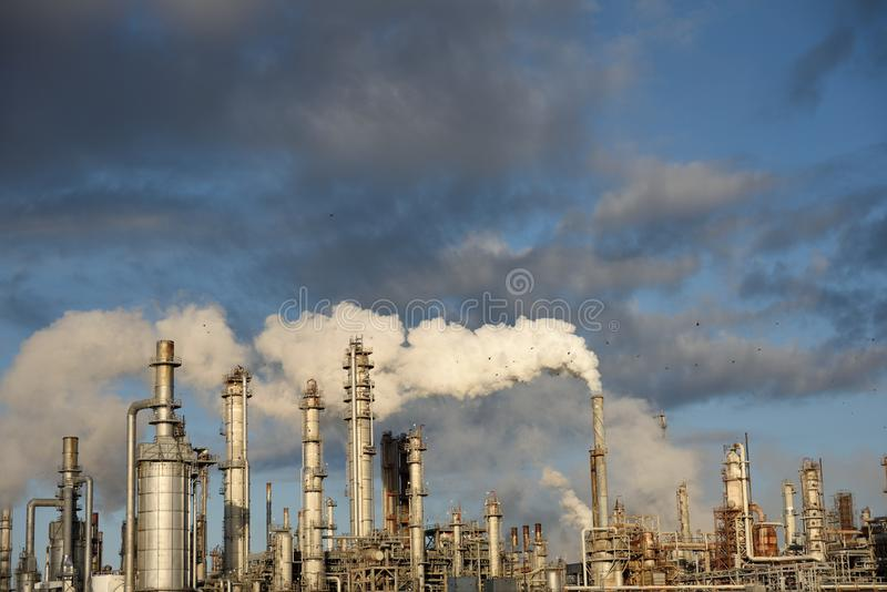 Smokestack emission cloud, petrochemical industrial refinery. Emission smoke plume rising from the smoke stack tower of an industrial oil and gas refinery in stock images