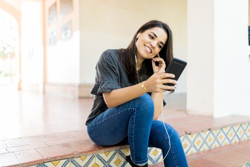 Emissione di radio d'ascolto della donna via l'applicazione mobile a Entran immagini stock libere da diritti