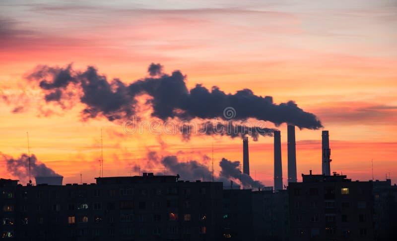 Emissioni della centrale elettrica durante l'alba in una città fotografia stock