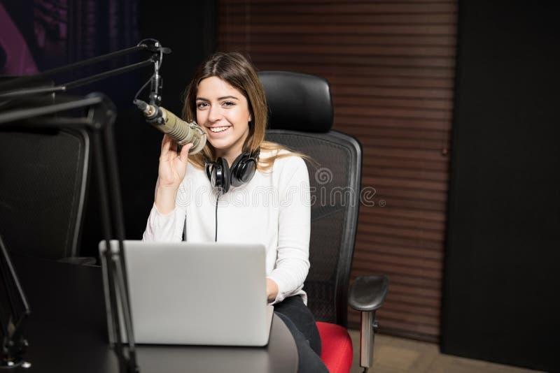 Emittente radiofonica femminile felice che ospita uno spettacolo dal vivo fotografia stock libera da diritti