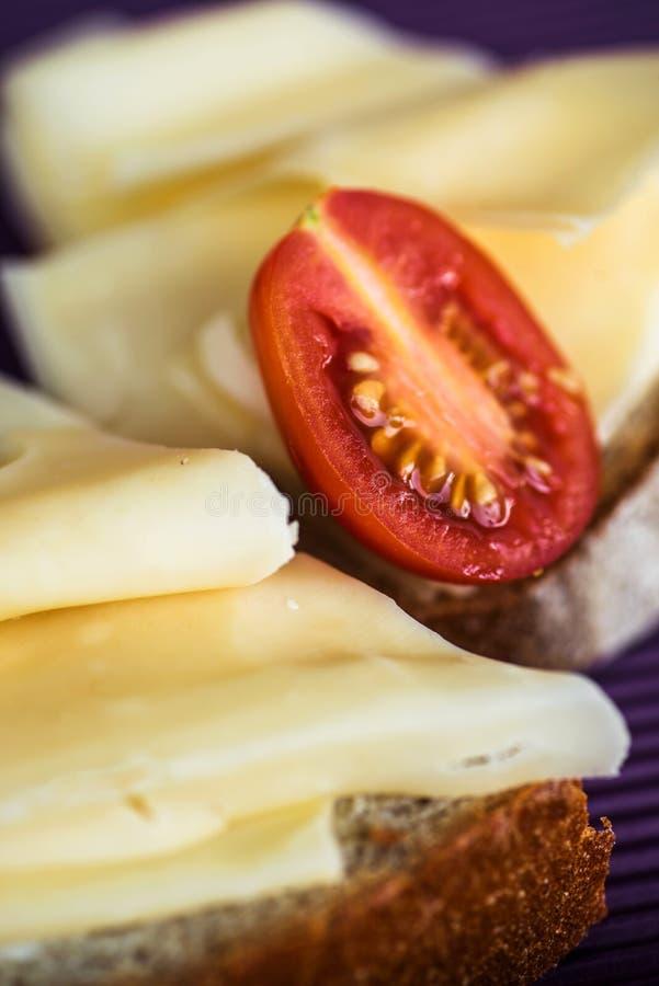 Emmental cchesse z pomidorem na chlebie, zbliżenie zdjęcie stock